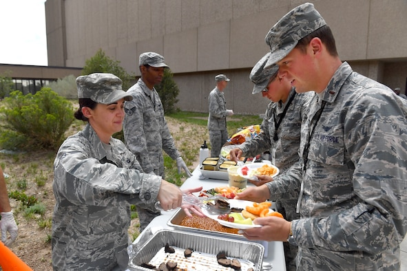 SCHRIEVER AIR FORCE BASE, Colo. – Tech. Sgt. Jacqulyn Rider, noncommissioned officer in charge of chapel operations for the 50th Space Wing Chaplain's office, serves members of the 50th Operations Group during a chapel-sponsored resiliency luncheon at Schriever Air Force Base, Colorado, 16 June, 2018. The Chaplain's office provides regular group lunches for members of the wing to instill unit cohesion and to support the units' commitment to resiliency. (U.S. Air Force Photo by Dennis Rogers)