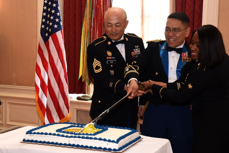 U.S. Army Sgt. 1st Class Scott Choi, Lt. Col. Yukio Kuniyuki, and Spc. Lakedra Emerson, members of the 344th Military Intelligence Battalion, cut the battalion cake in celebration of 100 years of signals intelligence and cryptology at the 344th MI BN Centennial Celebration in the Cactus Hotel, San Angelo, Texas, July 20, 2018. The battalion consists of three units, Alpha and Bravo Companies are located at Goodfellow Air Force Base, Texas, where Delta Company is located at Corry Station, Florida. (U.S. Air Force photo by Airman 1st Class Seraiah Hines/Released)
