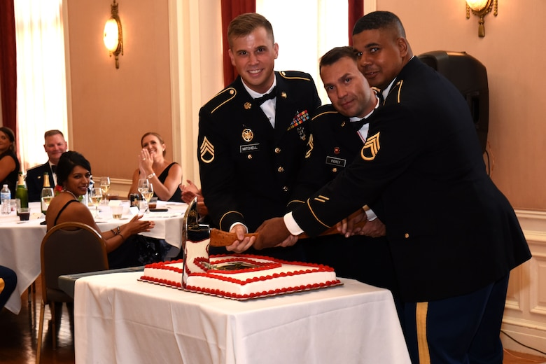 U.S. Army Staff Sgt. William Mitchell, Master Sgt. Jason Piercy and Staff Sgt. Benjamin Johnson, members of the 169th Engineer Battalion Firefighter Detachment, cut the battalion's cake during the 344th Military Intelligence Battalion Centennial Celebration in honor of 100 years of intelligence and cryptology at the Cactus Hotel, San Angelo, July 20, 2018. The cake is traditionally cut by the youngest individual in the BN, the oldest member in the BN and the highest ranking. (U.S. Air Force photo by Airman 1st Class Seraiah Hines/Released)