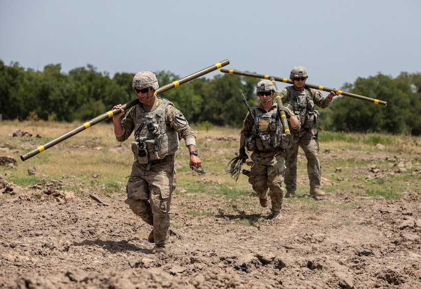 Combat engineers carry explosives during obstacle-breaching training.