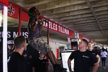 Marines with the Marine Forces Reserve Band encourage a Drum Corps International event attendee on the pull-up bar at the Cajundome Convention Center in Lafayette, Louisiana, July 23, 2018. The Drum Corps International creates a stage for the Marine Corps to engage in education, competition and the promotion of individual growth. (U.S. Marine Corps photo by Sgt. Nathaniel C. Cray)