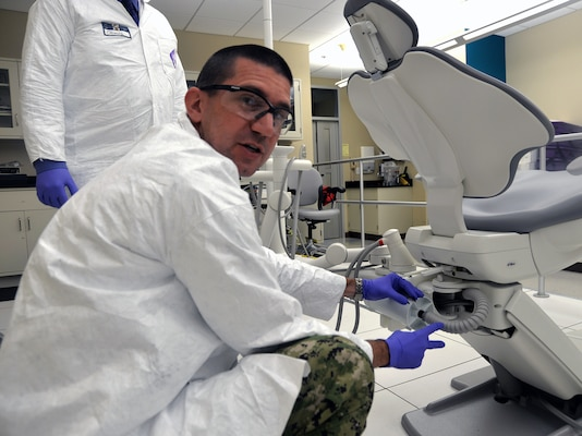 Lt. Cmdr. Nicholas Hamlin, Naval Medical Research Unit San Antonio Environmental Surveillance Department head and research dentist, demonstrates how an amalgam separator is attached to a dental chair and how it works in removing amalgam waste to prevent it from going into the wastewater system. Hamlin is part of a team of NAMRU-SA researchers who are involved in a project to develop a better prototype of the amalgam separator, a cylindrical device attached to a dental chair that filters amalgam, a mixture of metals including mercury, which is used by dentists for large teeth restorations and to fill in cavities.