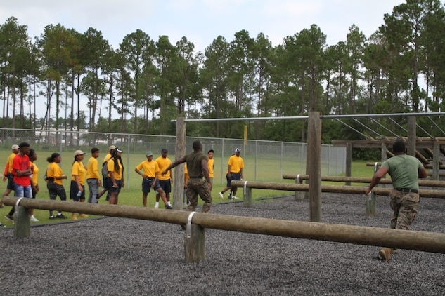 U. S. Marine Corps instructors perform a demonstration of proper techniques on maneuvering the obstacle course with dozens of Navy and Marine Corps Junior Reserve Officers Training Corps cadets. More than 40 cadets spent an intense five days at Marine Corps Logistics Base Albany for its first-ever summer camp. Each cadet experienced a week-long taste of basic leadership training. (U.S. Marine Corps photo by Re-Essa Buckels)