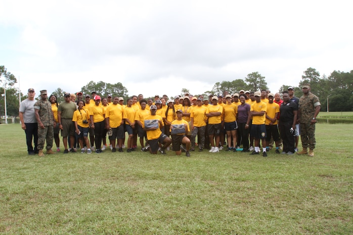 Marine Corps Logistics Base Albany Commanding Officer Colonel Alphonso Trimble (right) and Sergeant Major Johnny Higdon (left) take a group photo with Navy and Marine Corps Junior Reserve Officer Training Corps cadets and their instructors. More than 40 cadets spent an intense five days at Marine Corps Logistics Base Albany for its first-ever summer camp. Each cadet experienced a week-long taste of basic leadership training. (U.S. Marine Corps photo by Re-Essa Buckels)