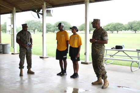 Marine Corps Logistics Base Albany Commanding Officer Colonel Alphonso Trimble (right) and Sergeant Major Johnny Higdon (left) recognizes the top two cadets who had the fastest times during the combat fitness tests. More than 40 cadets spent an intense five days at Marine Corps Logistics Base Albany for its first-ever summer camp. Each cadet experienced a week-long taste of basic leadership training. (U.S. Marine Corps photo by Re-Essa Buckels)