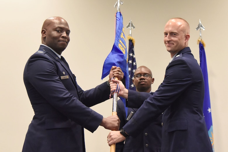 U.S. Air Force Col. Leo Lawson, Jr., 81st Training Group commander, passes the 333rd Training Squadron guidon to Lt. Col. Andrew Miller, 333rd TRS commander, during the 333rd TRS change of command ceremony in the Roberts Consolidated Aircraft Maintenance Facility at Keesler Air Force Base, Mississippi, July 24, 2018. The passing of the guidon is a ceremonial symbol of exchanging command from one commander to another. (U.S. Air Force photo by Kemberly Groue)