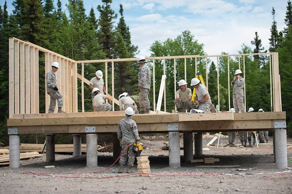 Members of the 149th Civil Engineer Squadron work to build a cabin.
