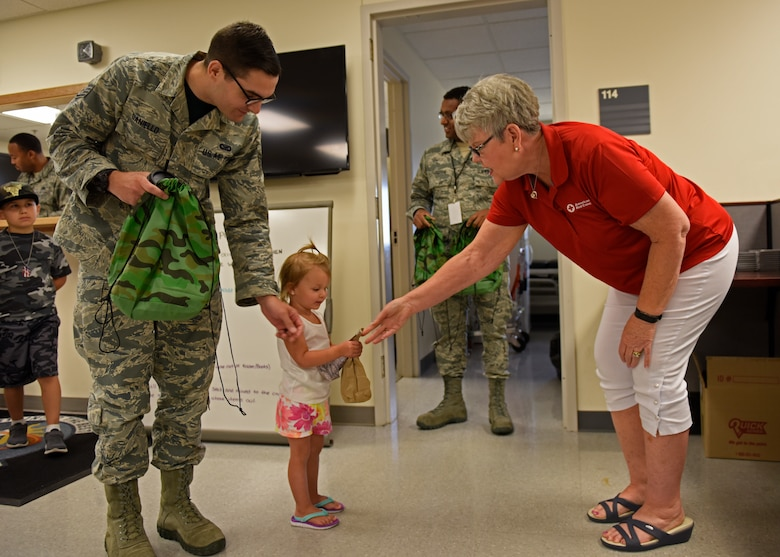 Sandi Meikel, American Red Cross volunteer, gives a military child a simulated Meal Ready to Eat during Operation Kids Understanding Deployment Operations at Fairchild Air Force Base, Washington , July 20, 2018. Operation KUDOS is designed to give children a visual understanding of deployments and provide families an opportunity to bond during an otherwise stressful life event. (U.S. Air Force photo/Airman 1st Class Jesenia Landaverde)