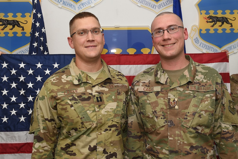 Two Airmen pose for a photo in front of an American flag