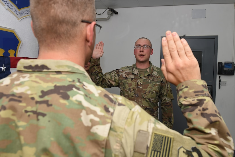 An Airman reads the oath of enlistment to his brother