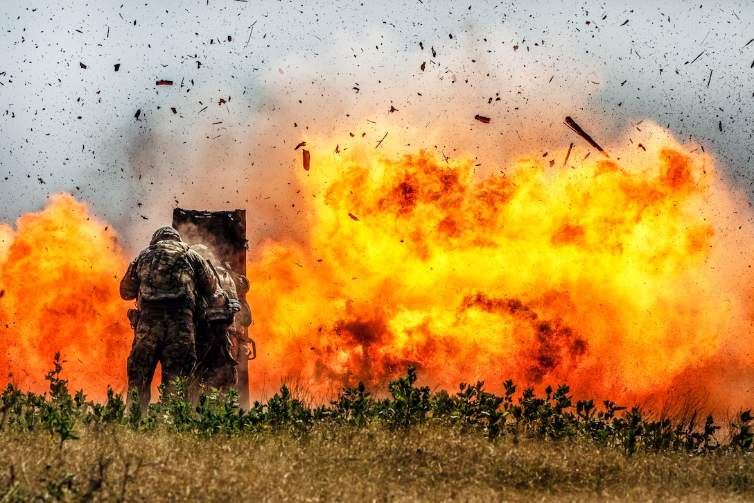 Soldiers brace themselves behind a shield as a detonation creates a huge fireball, sending pieces of concrete in the air.