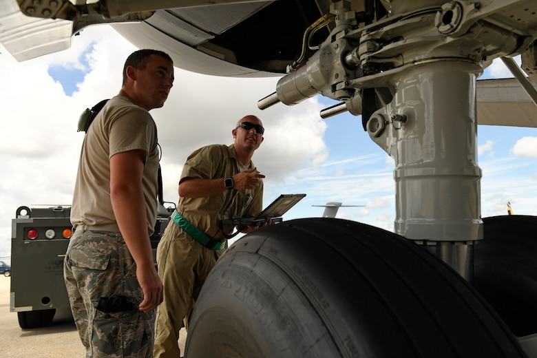 U.S. Air Force Tech. Sgt. Jason Smigelski (right) trains Airman 1st Class Wayne Chandler (left), both from the 145th Aircraft Maintenance Squadron (AMXS), on the proper procedure for connecting a tow bar to a C-17 Globemaster III aircraft at the the North Carolina Air National Guard Base, Charlotte Douglas International Airport, July 24, 2018. Since the aircraft conversion in April, the 145th AMXS is working to train maintenance personnel with a goal of them being fully qualified.