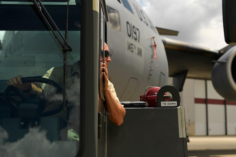 U.S. Air Force Tech. Sgt. Jason Smigelski, 145th Aircraft Maintenance Squadron, looks at his spotter for hand and arm signals to direct the towing of a C-17 Globemaster III into position at the North Carolina Air National Guard Base, Charlotte Douglas International Airport, July 24, 2018. Maintenance personnel use hand and arm signals to direct each other and  park the airframe in the proper position on the flightline.