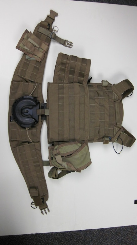 A military mounting system (MOLLE) and a hip belt with a Ruck Dock receiver is shown. The Ruck Dock receiver is part of a two piece system that allows a person carrying a MOLLE or other backpack  evenly distribute the weight and quickly couple or decouple the system. The technology was developed by the Air Force Research Laboratory 711th Human Performance Wing and licensed to Newcomer Arms LLC of New Jersey. (Photo courtesy of Newcomer Arms.)