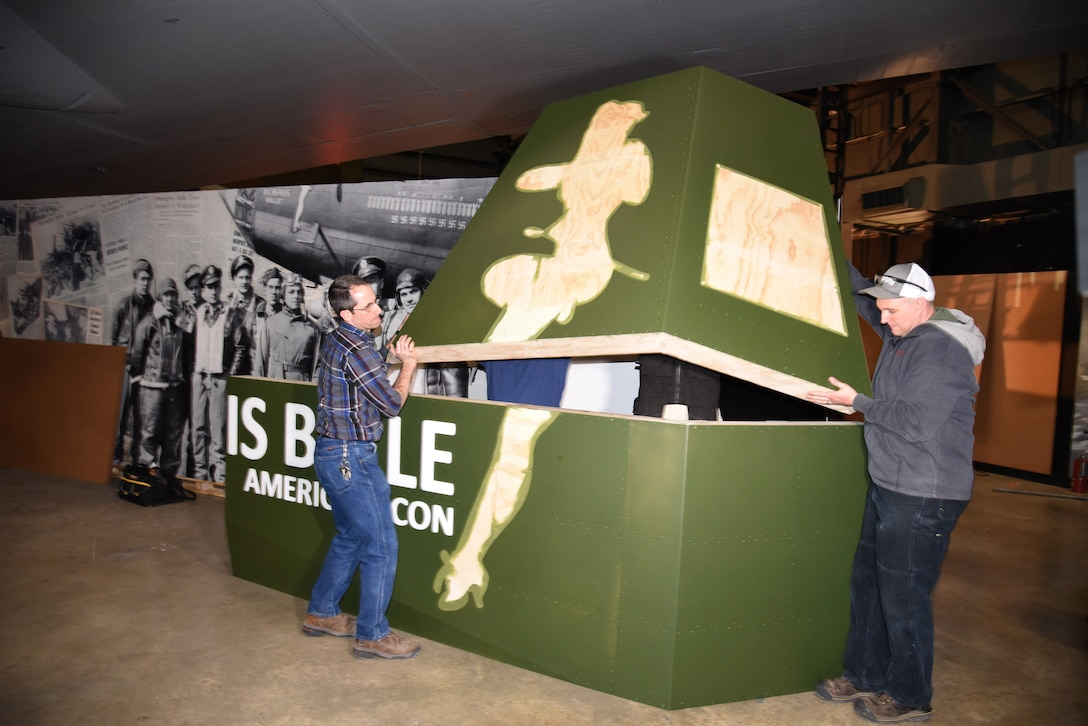 Museum Exhibit Specialists Caleb Still(L) and Mike Foster(R) install display pieces for the Memphis Belle Exhibit in the WWII Gallery. (U.S. Air Force photo by Ken LaRock)