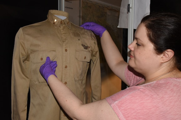 Museum Conservator Jennifer Myers prepares artifacts for display in the WWII Gallery.