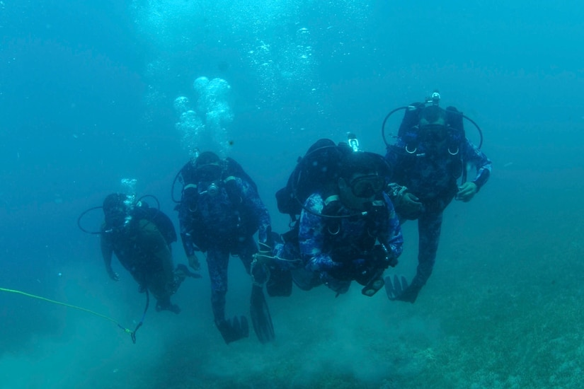 Sailors scuba dive during a military exercise.