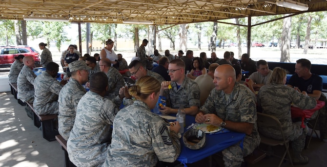 Airmen from the 301st Fighter Wing's force support squadron, wing staff, communication squadron, and operations group take a break from unit training assembly duties to eat a barbecue lunch provided by the Dallas/Fort Worth United Service Organization (USO), July 15, 2018. The USO works to lift the spirits of America's troops and their families at USO Centers and through morale-boosting and family-strengthening programs targeting service members stationed in DFW. (U.S. Air Force photo by Tech. Sgt. Charles Taylor)