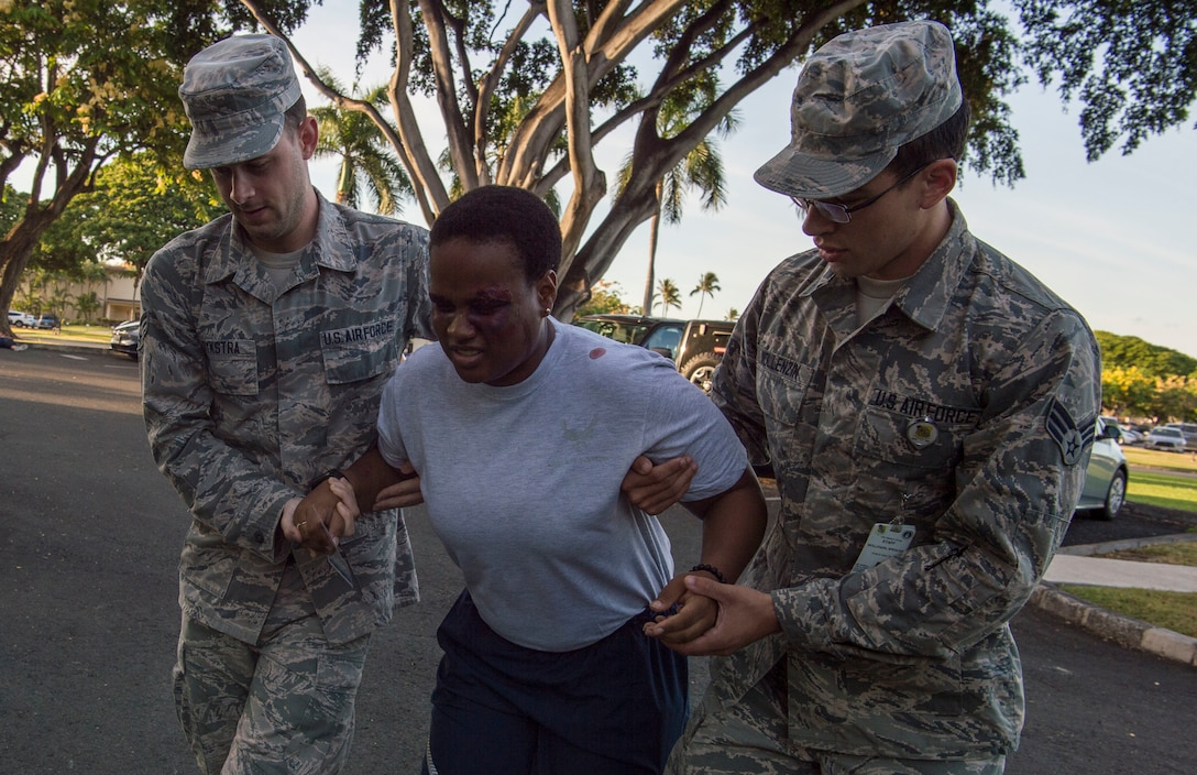 Senior Airman Logan Dykstra and Senior Airman Spencer Wollenzin, 15th Medical Group, provide aid to Staff Sgt. Nyasia Clark during a mass-casualty scenario for Rim of the Pacific exercise at Joint Base Pearl Harbor-Hickam, July 12, 2018. Twenty-five nations, 46 ships, five submarines, about 200 aircraft and 25,000 personnel are participating in RIMPAC from June 27 to Aug. 2 in and around the Hawaiian Islands and Southern California. The world's largest international maritime exercise, RIMPAC provides a unique training opportunity while fostering and sustaining cooperative relationships among participants critical to ensuring the safety of sea lanes and security of the world's oceans. RIMPAC 2018 is the 26th exercise in the series that began in 1971. (U.S. Air Force photo by Tech. Sgt. Heather Redman)