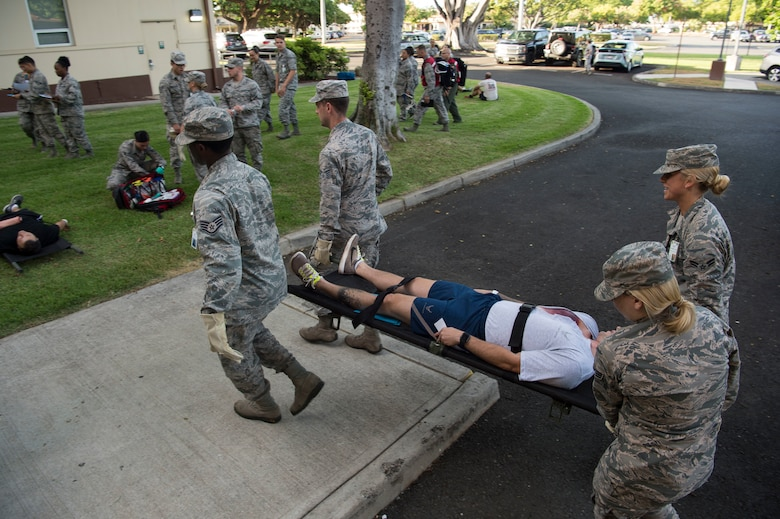 Airmen from the 15th Medical Group, work together to carry injured a simulated injured person to a centralized point at the Medical Group, during a mass-casualty scenario for Rim of the Pacific July 12, 2018. Twenty-five nations, 46 ships, five submarines, about 200 aircraft and 25,000 personnel are participating in RIMPAC from June 27 to Aug. 2 in and around the Hawaiian Islands and Southern California. The world's largest international maritime exercise, RIMPAC provides a unique training opportunity while fostering and sustaining cooperative relationships among participants critical to ensuring the safety of sea lanes and security of the world's oceans. RIMPAC 2018 is the 26th exercise in the series that began in 1971. (U.S. Air Force photo by Tech. Sgt. Heather Redman)