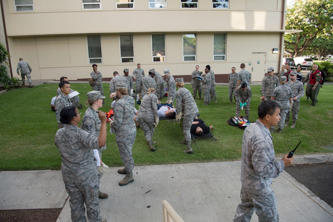 Airmen from the 15th Medical Group work together to provide medical aid for mock casualties during a mass-casualty scenario during the Rim of the Pacific exercise at Joint Base Pearl Harbor-Hickam, July 12, 2018. Twenty-five nations, 46 ships, five submarines, about 200 aircraft and 25,000 personnel are participating in RIMPAC from June 27 to Aug. 2 in and around the Hawaiian Islands and Southern California. The world's largest international maritime exercise, RIMPAC provides a unique training opportunity while fostering and sustaining cooperative relationships among participants critical to ensuring the safety of sea lanes and security of the world's oceans. RIMPAC 2018 is the 26th exercise in the series that began in 1971. (U.S. Air Force photo by Tech. Sgt. Heather Redman)