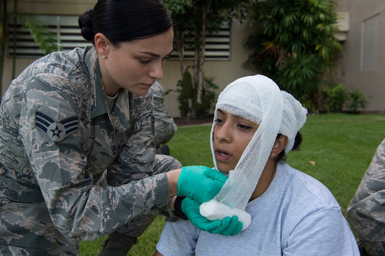 Senior Airman Samantha King, 15th Medical Group, bandages Capt. Elizabeth Perryman's simulated wounds during a mass-casualty scenario for Rim of the Pacific  exercise at Joint Base Pearl Harbor-Hickam, July 12, 2018. Twenty-five nations, 46 ships, five submarines, about 200 aircraft and 25,000 personnel are participating in RIMPAC from June 27 to Aug. 2 in and around the Hawaiian Islands and Southern California. The world's largest international maritime exercise, RIMPAC provides a unique training opportunity while fostering and sustaining cooperative relationships among participants critical to ensuring the safety of sea lanes and security of the world's oceans. RIMPAC 2018 is the 26th exercise in the series that began in 1971. (U.S. Air Force photo by Tech. Sgt. Heather Redman)