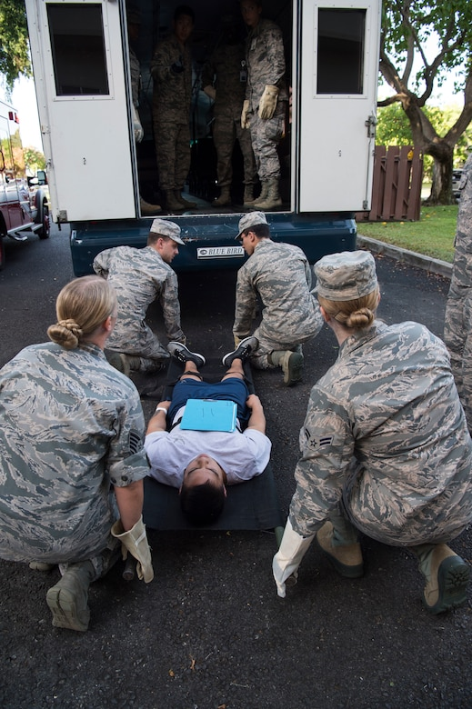 Airmen from the 15th Medical Group, work together to load mock casualties into a medical evacuation bus during a mass-casualty scenario for Rim of the Pacific exercise, Joint Base Pearl Harbor-Hickam, July 12. Twenty-five nations, 46 ships, five submarines, about 200 aircraft and 25,000 personnel are participating in RIMPAC from June 27 to Aug. 2 in and around the Hawaiian Islands and Southern California. The world's largest international maritime exercise, RIMPAC provides a unique training opportunity while fostering and sustaining cooperative relationships among participants critical to ensuring the safety of sea lanes and security of the world's oceans. RIMPAC 2018 is the 26th exercise in the series that began in 1971. (U.S. Air Force photo by Tech. Sgt. Heather Redman/Released)