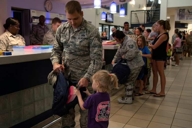 An Airman helps his daughter fill her backpack with supplies at the Back-To-School Brigade, July 25, 2018, at Moody Air Force Base, Ga. With the help of Operation Homefront and the local community, the event provided Moody Airmen, grades E-1 through E-6, with school supplies. (U.S. Air Force photo by Airman Taryn Butler)