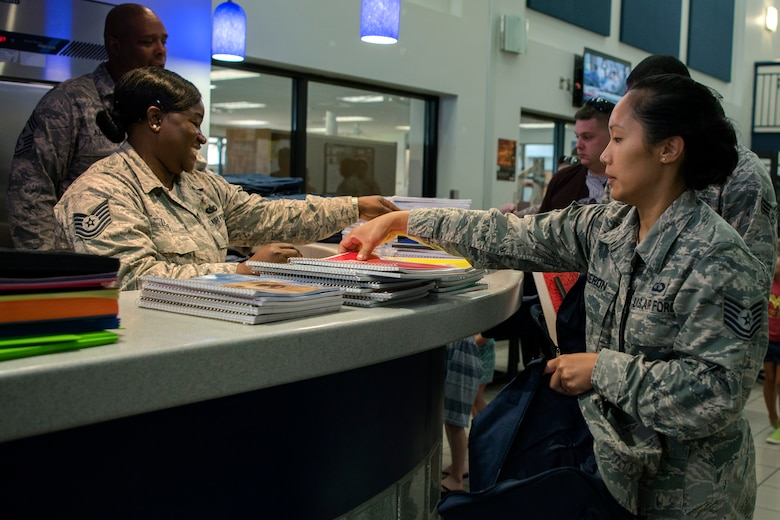 An Airman picks up a notebook at the Back-To-School Brigade, July 25, 2018, at Moody Air Force Base, Ga. With the help of Operation Homefront and the local community, the event provided Moody Airmen, grades E-1 through E-6, with school supplies. (U.S. Air Force photo by Airman Taryn Butler)
