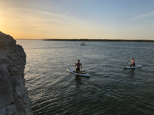 Senior Airman Brandon Taylor, 47th Civil Engineer Squadron firefighter, and Staff Sgt. Kevin Vaughn, 434th Flying Training Squadron aviation resource management NCO in charge, enjoy an evening of kayaking on Lake Amistad, near Del Rio, Texas. Alex Aguilar, 47th Flying Training Wing occupational safety specialist warns, for Laughlin's boaters, that without a depth finder or knowledge of the area, damage could occur on the boats from either objects in the water sticking up or phantom islands that appear when the water is low. (U.S. Air Force photo by Senior Airman Benjamin Valmoja)