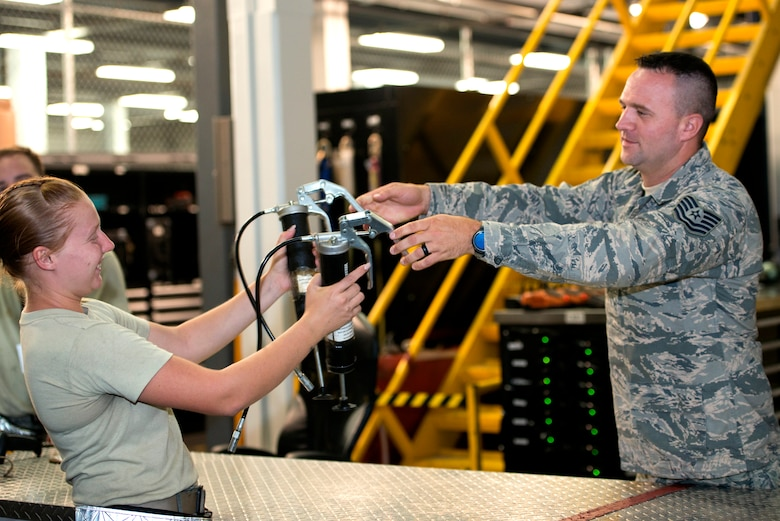 U.S. Air Force TSgt. Eric Holton, NCO in charge of the maintenance flight support section assigned to the 6th Maintenance Squadron signs out hazardous materials to Airman 1st Class Amanda Brundage, an inspections crew chief assigned to the 6th MXS at MacDill Air Force Base Florida, July 26, 2018.