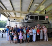 Members of former Irvington Site employee Stephen Sema's family pose in front of the Sarge, a new survey vessel during a christening ceremony July 13, 2018, in Irvington, Ala.