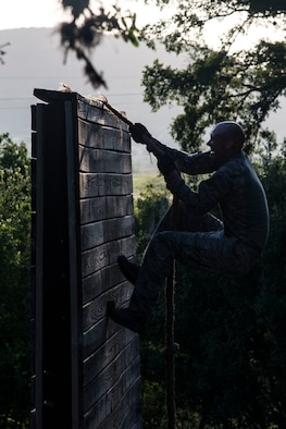 Capt. Nathan Spradley, 902nd Security Forces Squadron operations officer, climbs an obstacle July 23, 2018, at Joint Base San Antonio-Camp Bullis, Texas in preparation for the 2018 Defender Challenge. The competition will pit security forces teams against each other in realistic weapons, dismounted operations and relay challenge events. (U.S. Air Force photo by Senior Airman Stormy Archer)