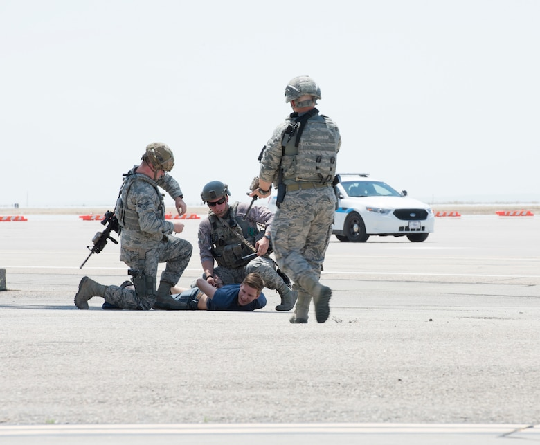 Members of the 366th Security Forces squadron arrest Airman 1st Class Trevor Gordnier, 366th Fighter Wing broadcast journalist, during a Force Protection Condition exercise, July 23, 2018, at Mountain Home Air Force Base, Idaho. The exercise tested the wing's ability to execute the proper procedures associated with different FPCONs during a wide variety of scenarios. (U.S. Air Force photo by Airman 1st Class Alaysia Berry)