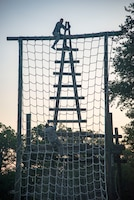Security Forces Airmen climb and obstacle July 23, 2018, at Joint Base San Antonio-Camp Bullis, Texas in preparation for the 2018 Defender Challenge. The competition will pit security forces teams against each other in realistic weapons, dismounted operations and relay challenge events. (U.S. Air Force photo by Senior Airman Stormy Archer)