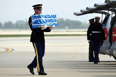 A United Nations Honor Guard member carries remains during a dignified return ceremony at Osan Air Base, South Korea.
