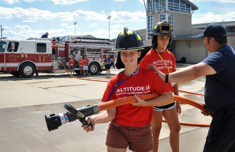 Dakota Wagner (Left) and Savannah Smith (Center) learn what it's like to be a firefighter during their second day of Air Camp at Wright-Patterson Air Force, Ohio. July 17, 2018.