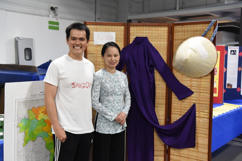 Airman 1st Class Luan Tong, a 319th Comptroller Squadron financial operations technician, and his wife, Linh Le, pose for a photo June 20, 2018, at Grand Forks Air Force Base, North Dakota. Tong said his booth was based on Vietnam culture, where he showed base residents clothing styles, tea sets and a food dish from his native country. (U.S. Air Force photo by Airman 1st Class Melody Wolff)