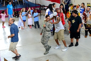 Airmen and community members dance in a circle at Diversity Day July 19, 2018, on Columbus Air Force Base, Mississippi. The Mystic Wind Choctaw Social Dancers asked the attendees to get involved in a few of their traditional dances. (U.S. Air Force photo by Airman 1st Class Beaux Hebert)