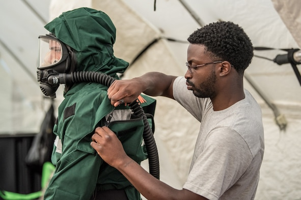 Airman First Class Anthony Cirwithian (right), a member of the Kentucky Air National Guard's Fatality Search and Recovery Team, zips up a MT94 chemical, biological, radiological and nuclear defense suit for Senior Airman Ben Bohannon, another FSRT member, at Rough River State Resort Park in Falls of Rough, Ky., on July 18, 2018. Thirteen members of the 123rd Airlift Wing participated in the three-day exercise to simulate the recovery and repatriation of fallen service members. (U.S. Air National Guard photo by Master Sgt. Phil Speck)