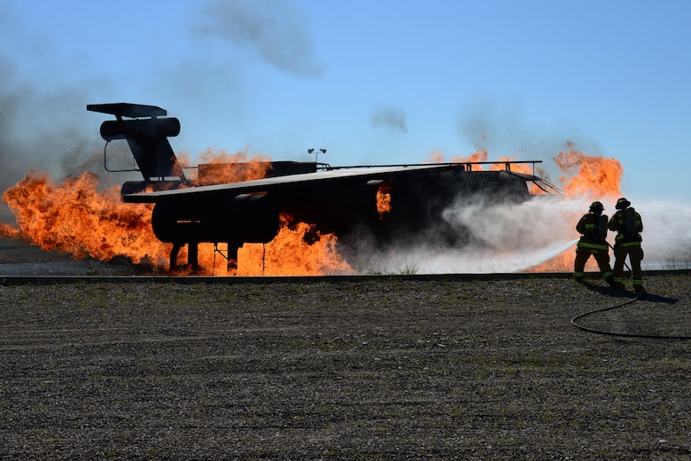 Airman 1st Class Dean York, left, and Staff Sgt. Peter Kuriwai, 341st Civil Engineer Squadron firefighters, attempt to put out a fire during an exercise July 18, 2018, at Malmstrom Air Force Base, Mont. Airmen with the 341st CES ran through aircraft fire procedures in case a disaster occurs. (U.S. Air Force photo by Airman 1st Class Tristan Truesdell)