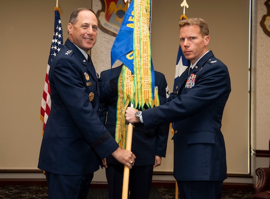 Lt. Gen. Lee Levy II, Air Force Sustainment Command commander, presents the 635th Supply Chain Operations Wing guidon to Col. Robert Henderson