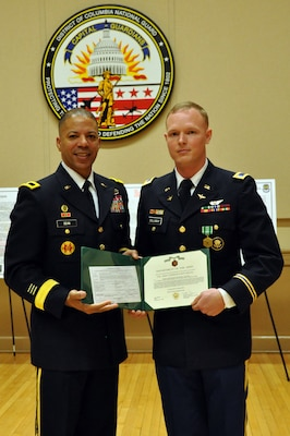 Brig. Gen. Aaron R. Dean, II, adjutant general, District of Columbia National Guard, presents Warrant Officer Jonathan Callaway with an Army Commendation Medal during a reception celebrating 100 years of the U.S. Army warrant officer corps, on Feb. 27, in the Commanding General's Conference Room of the D.C. Armory, in Washington, D.C. Callaway was presented the award for being the distinguished honor graduate in his Army rotary wing pilot course. (U.S. Army National Guard photo and caption by Spc. Kevin Valentine/released)