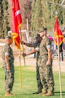 Colonel Sekou Karega, outgoing commanding officer, receives the command colors from base Sergeant Major Sergio Martinezruiz prior to relinquishing  to Col. Craig Clemans, incoming base commander, during the change of command ceremony aboard Marine Corps Logistics Base Barstow, Calif., July 19.