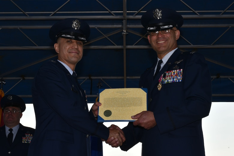 U.S. Air Force Col. Ricky Mills, 17th Training Wing commander, presents Col. Alex Ganster, 17th Training Group outgoing commander, with a Legion of Merit certificate during the 17th TRG Change of Command on the parade field on Goodfellow Air Force Base, Texas, July 27, 2018. For two years, Ganster led the group's four squadrons and one detachment, with 2,472 personnel and $400 million in resources, to graduate more than 28,500 students from all five branches and more than 25 nations. (U.S. Air Force photo by Senior Airman Randall Moose/Released)