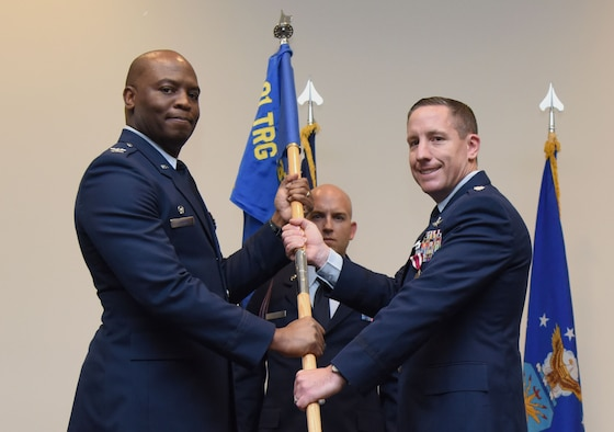U.S. Air Force Col. Leo Lawson, Jr., 81st Training Group commander, takes the 338th Training Squadron guidon from Lt. Col. Michael Zink, outgoing 338th TRS commander, during the 338th TRS change of command ceremony in the Roberts Consolidated Aircraft Maintenance Facility at Keesler Air Force Base, Mississippi, July 26, 2018. The passing of the guidon is a ceremonial symbol of exchanging command from one commander to another. (U.S. Air Force photo by Kemberly Groue)
