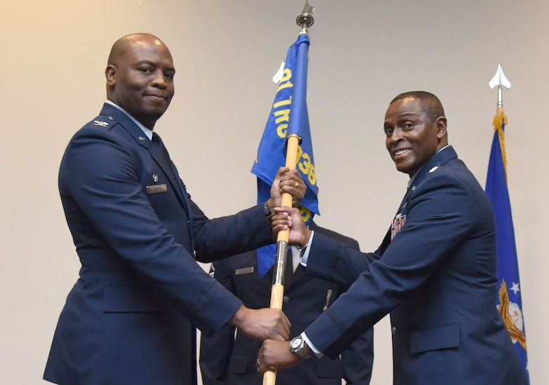 U.S. Air Force Col. Leo Lawson, Jr., 81st Training Group commander, passes the 338th Training Squadron guidon to Lt. Col. Andre Johnson, incoming 338th TRS commander, during the 338th TRS change of command ceremony in the Roberts Consolidated Aircraft Maintenance Facility at Keesler Air Force Base, Mississippi, July 26, 2018. The passing of the guidon is a ceremonial symbol of exchanging command from one commander to another. (U.S. Air Force photo by Kemberly Groue)
