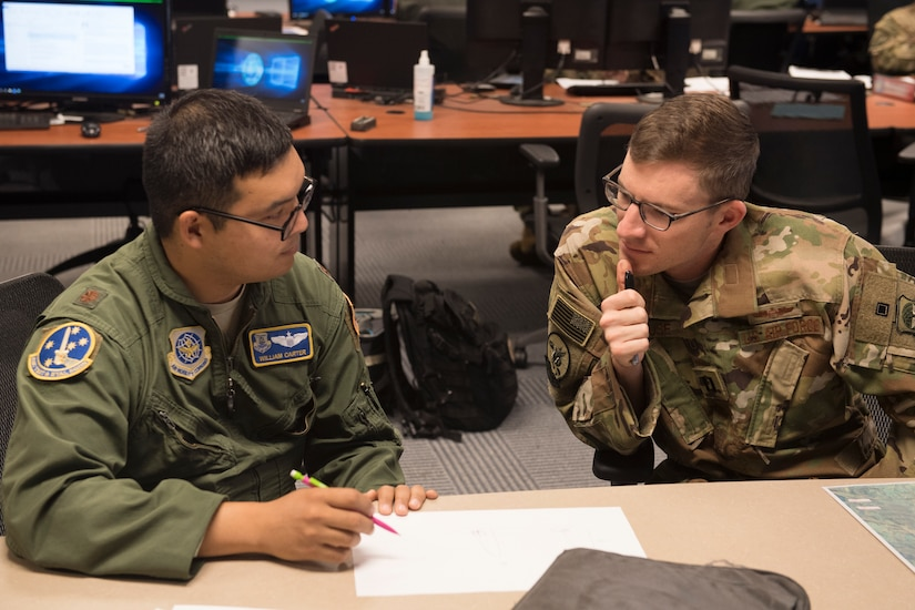 Maj. William Carter, Air Mobility Command Test and Evaluation Squadron Pilot-Directed Airdrop test Test Director, conducts preflight planning July 19, 2018, with Capt. Nick Krause, a pilot from the 8th Airlift Squadron at Joint Base Lewis-McChord, Wash.