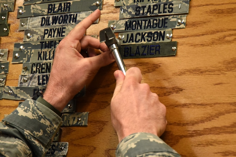 U.S. Air Force Chief Master Sgt. Stefan Blazier, 363rd Intelligence, Surveillance and Reconnaissance Wing command chief, tacks his name tape to the instructor wall in the Heritage Hall of the 315th Training Squadron on Goodfellow Air Force Base, Texas, July 26, 2018. This hall is used to honor instructors who have taught at the squadron over the years. (U.S. Air Force photo by Airman 1st Class Seraiah Hines/Released)