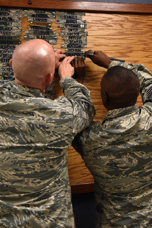 U.S. Air Force Chief Master Sgt. Stefan Blazier, 363rd Intelligance, Survelillance and Reconnaissance Wing command chief, assists Chief Master Sgt. Lavor Kirkpatrick, 17th Training Wing command chief, with tacking his name tape to the board in Heritage Hall of the 315th Training Squadron at Goodfellow Air Force Base, Texas, July 26, 2018. Blazier and Kirkpatrick have been stationed all over the world together and were once instructors for the 315th TRS at Goodfellow. (U.S. Air Force photo by Airman 1st Class Seraiah Hines/Released)